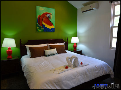 King bed and painting of Scarlett Macaw